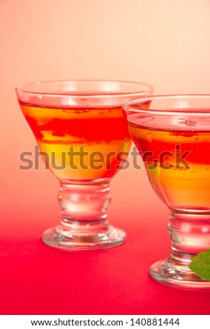 Two glasses with bright fruit jelly, closeup, on a pink background