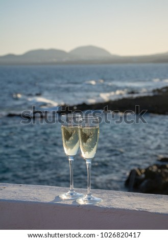 Two glasses with champagne or cava sparkling wine served outside on terrace, luxury resort with sea view, romantic vacation