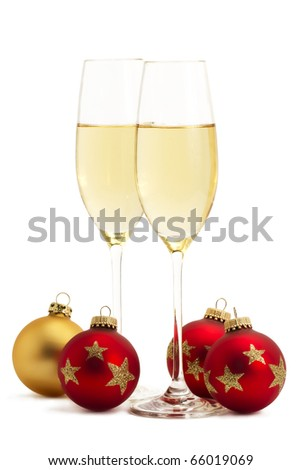 two glasses with champagne with one golden and three red christmas balls on white background - stock photo