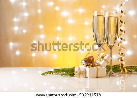 Two glasses with champange, fir tree branch, gift boxes and christmas decorations on a yellow background with lights of garland.  New year and Christmas.