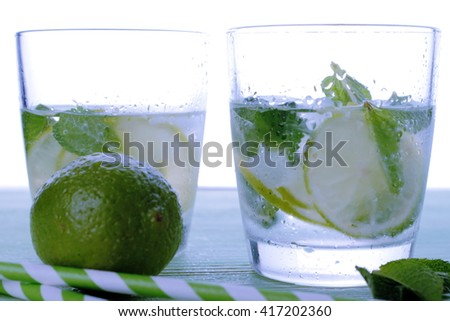 Two glasses with cocktail and ice with lime slice on table. - stock photo