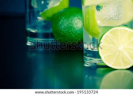two glasses with cocktail and ice with lime slice on table, disco club atmosphere - stock photo