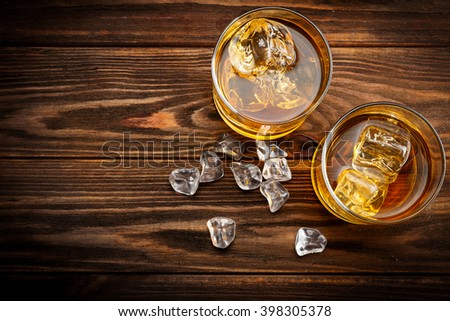 Two glasses with ice and whiskey on wooden background (top view)