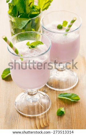 Two glasses with milk cocktail decorated with mint leaves - stock photo