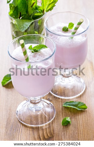 Two glasses with milk cocktail decorated with mint leaves