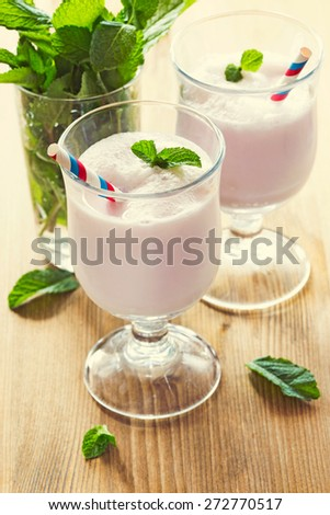 Two glasses with milk cocktail decorated with mint leaves. Vintage toning