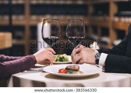 Two glasses with red wine on a table with white tablecloth. Shelves with wine and candles are on background.