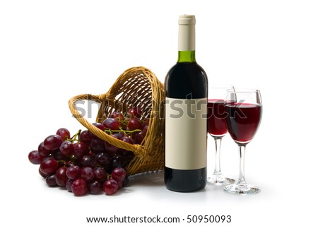Two glasses with red wine on a white background. A dark wine bottle with a empty label. Red ripe grape in wooden basket. - stock photo