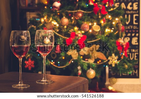 Two glasses with red wine on table. Blurred Christmas tree in background.