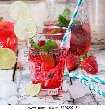 Two glasses with retro cocktail tubes and glass jug of homemade strawberry lemonade, served with fresh strawberries, mint, lime and ice cubes over old white wooden table. Square image - stock photo
