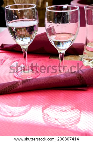 Two glasses with water, their reflection and spilled water on the paper tablecloth. Restaurant's terrace in sunny day. Picardy, France. - stock photo