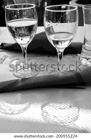 Two glasses with water, their reflection and spilled water on the paper tablecloth. Restaurant's terrace in sunny day. Picardy, France. Aged photo. Black and white. - stock photo