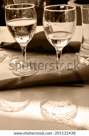 Two glasses with water, their reflection and spilled water on the paper tablecloth. Restaurant's terrace in sunny day. Picardy, France. Aged photo. Sepia. - stock photo