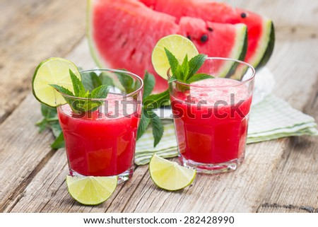 Two glasses with watermelon smoothies with lime and mint - stock photo