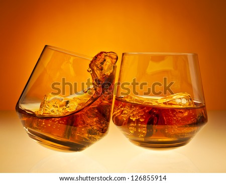 Two glasses with whisky on the rocks clicking together, one spilling over - stock photo