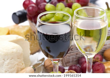 two glasses with white and red wine, cheese and grapes, close-up