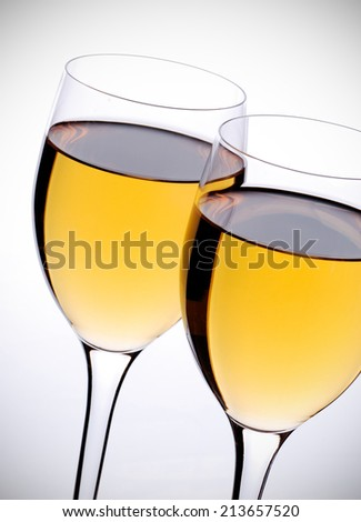 two glasses with white wine on white background