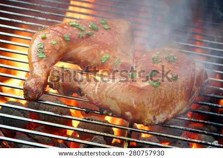 Two Glazed Chicken Quarter On The Hot BBQ Charcoal Flaming Grill Close-up. - stock photo