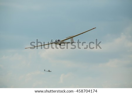 Two gliders soar in the air on a summer day. The glider gliding in the blue sky, glider flight