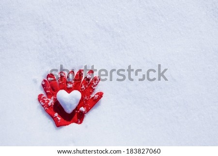 Two gloves in the snow with a heart on them. - stock photo