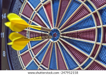 Two goals dart in bulls eye of dartboard close up - stock photo
