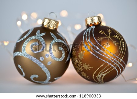 Two gold Christmas decorations with decorative lights on gray background