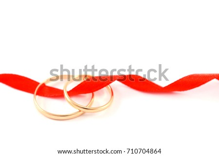Two gold engagement rings with a curled red satin ribbon on white