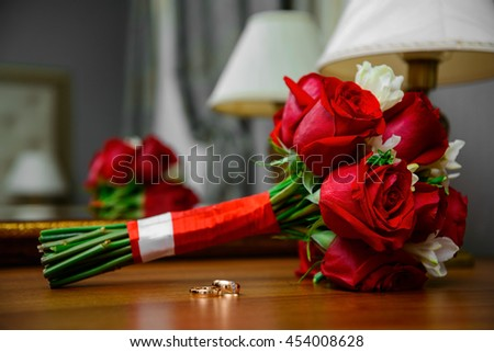 two gold rings and bouquet of red roses lying on a wooden table under a lamp at the mirror - stock photo