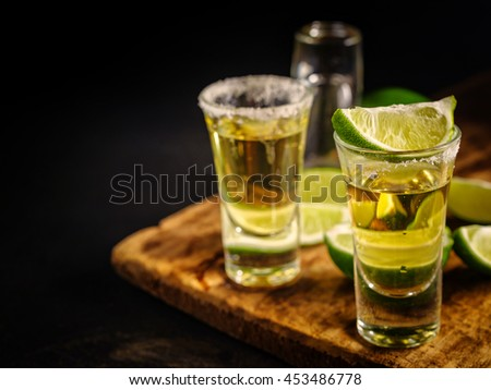 Two Gold tequila shots with lime, copy space on left side. Gold Mexican tequila on wooden background. Alcohol drink, selective focus.