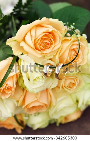 two gold wedding rings on a bouquet of roses