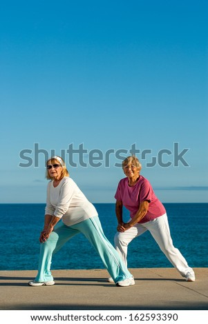 Two golden age women stretching legs at seafront.