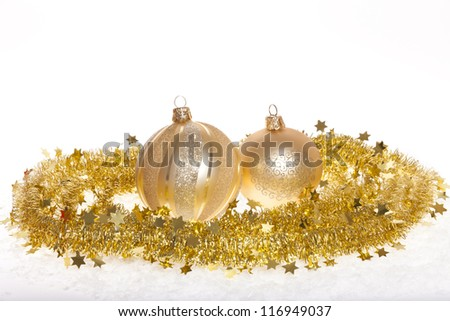 Two golden christmas baubles decorated with gold tinsel isolated on white