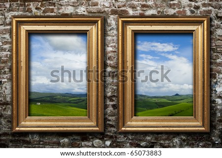Two golden frames on a dark brick wall - stock photo