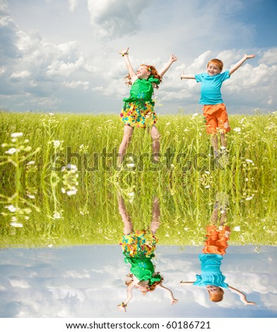 Two golden-haired children playin the field. Specular reflection in water - stock photo