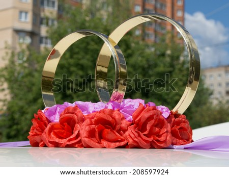 Two golden rings and artificial flowers as wedding car decoration - stock photo