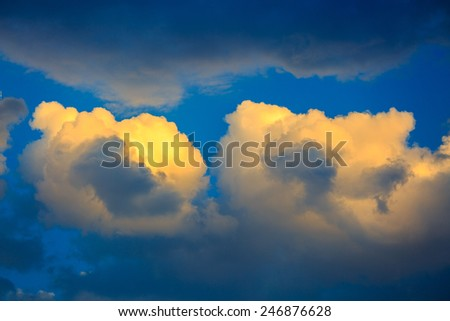 Two golden sunset clouds on a blue sky - stock photo