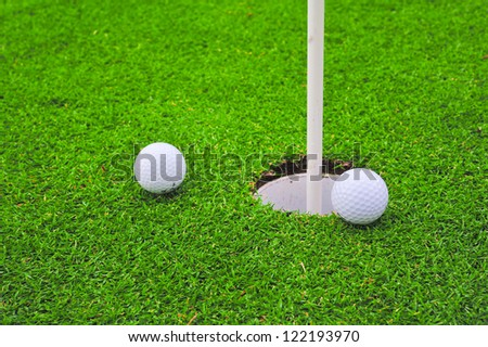 Two golf balls on golf course putting green