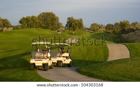 Two golf carts stand on the course path beside the ninth hole mature sport - stock photo