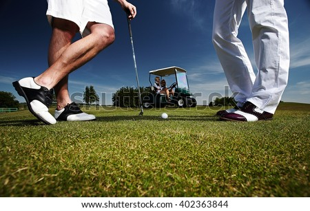 Two golf player on a green field and a golf car. - stock photo