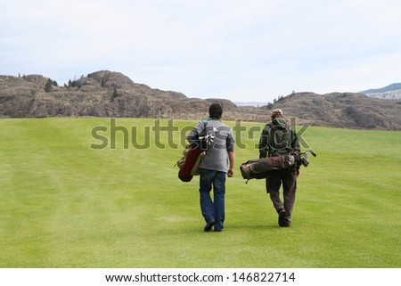 Two golfers playing golf in the field. - stock photo