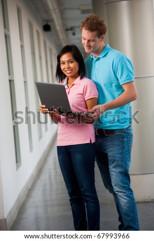 Two good looking college students share a laptop on university campus.  20s female Asian Thai model of Chinese descent at camera.  20s tall male caucasian model British nationality looking screen. - stock photo
