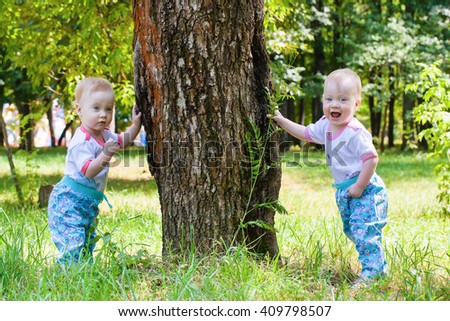 Two gorgeous girls twins walking on green grass with pleasure