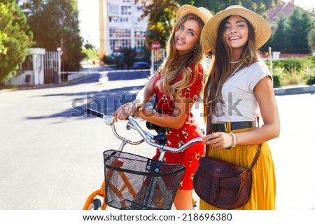 Two gorgeous pretty sensual girls with retro trendy bikes posing at the street at evening sun light, wearing vintage dresses and hats. Fashion portrait of beat fiends having fun. - stock photo