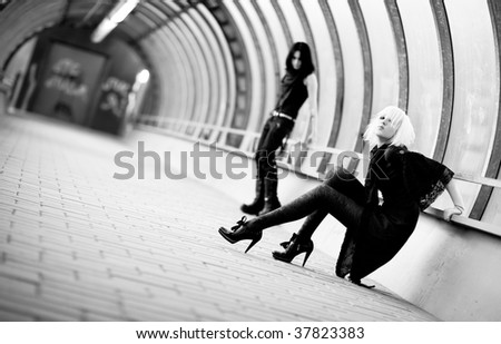 Two goth women in industrial tunnel. Contrast black and white colors. - stock photo
