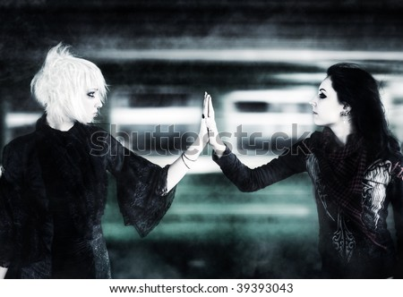 Two goth women touching hands on moving train background. - stock photo