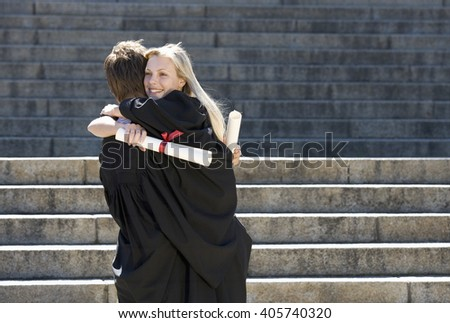 Two graduates embracing - stock photo