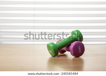 Two green and pink(magenta) dumbbells on the wood office desk(table) behind white blind. - stock photo