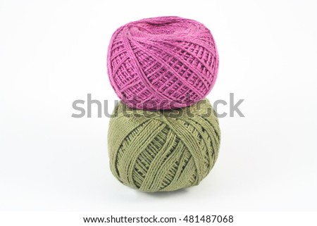 Two green and purple balls of yarn on white