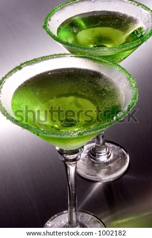 Two green apple martini's with green colored sugar around the rims chilled to perfection on a stainless steel surface.