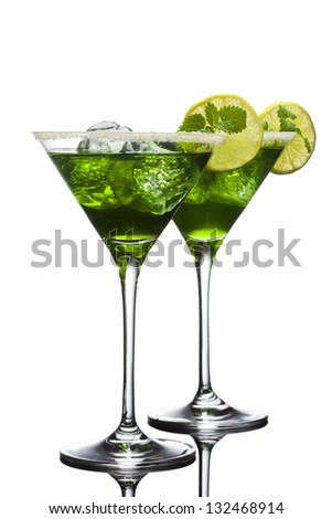 Two green cocktails with lime slices, mint leaves, ice cubes and brown sugar isolated on white